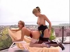 Lesbians play with dildo on terrace